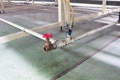 La valvola rossa con il tubo dell'aria sul sistema pneumatico Fotografia Stock