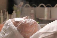 La vapeur chaude est dirigée vers le visage d'une femme dans un salon de cosmétologie La fille sur la procédure d'augmenter des p photo libre de droits