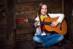 La vaquera linda del adolescente toca la guitarra Foto de archivo libre de regalías