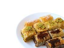 La variété de pâtisseries mouthwatering de baklava a servi du plat blanc d'isolement sur le fond blanc photos libres de droits