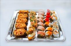 La variedad de sushi delicioso del corte sirvió en un disco de plata en una superficie blanca - foco selectivo fotografía de archivo