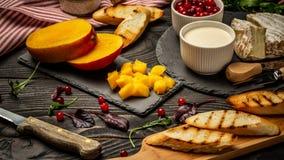 La varietà di ingredienti alimentari freschi per il pane tostato al forno dei panini degli spuntini con formaggio cremoso ed il m fotografia stock