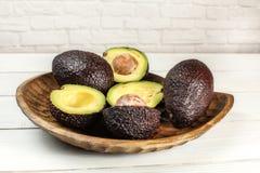 La varietà marrone matura del bilse degli avocado alcuni di loro è dimezzato in ciotola scolpita di legno, sullo scrittorio dei fotografia stock