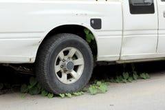 La vecchia automobile ha parcheggiato le erbacce di molto tempo sulla ruota Immagine Stock Libera da Diritti