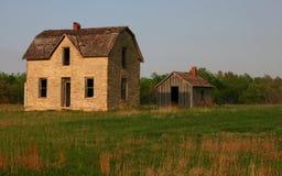 La vecchia azienda agricola abbandonata si dirige ancora la seduta vuota attraverso il midwest Fotografia Stock
