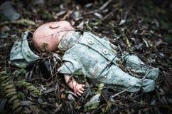 La vecchia bamboletta rotta abbandonata si decompone in foresta spaventosa Fotografia Stock Libera da Diritti