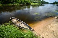 La vecchia barca legata con la catena ed il lucchetto all'estate verde contano al noo Fotografie Stock