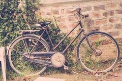La vecchia bici pende contro un vecchio muro di mattoni, annata Fotografie Stock Libere da Diritti
