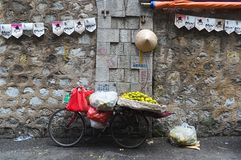 La vecchia bicicletta con le arance fruttifica sul mercato di strada vicino alla parete Immagini Stock Libere da Diritti