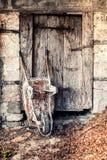 La vecchia carriola arrugginita ha peso contro la porta di legno antica Fotografie Stock