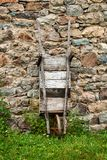 La vecchia carriola di legno ha peso contro una parete di pietra Immagine Stock Libera da Diritti