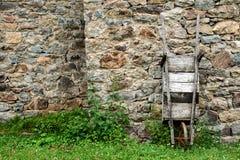 La vecchia carriola di legno ha peso contro una parete di pietra Fotografia Stock
