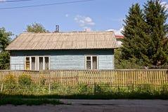 La vecchia casa rurale di legno dietro un di legno recinta la vegetazione Fotografia Stock Libera da Diritti
