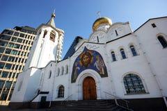 La vecchia chiesa con un campanile e una costruzione moderna Fotografia Stock