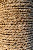 La vecchia corda di manila ha avvolto accurato e stretto intorno al palo Fotografia Stock