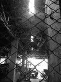 La vecchia costruzione abbandonata tramite il recinto della maglia fotografie stock libere da diritti