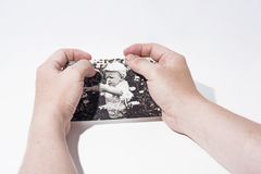 La vecchia foto di carta dentro equipaggia le mani immagine stock