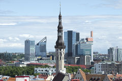 La vecchia guglia del municipio medievale sui precedenti della città moderna Tallinn, Estonia Fotografia Stock