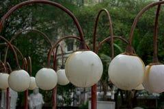 La vecchia lampada, palla bianca ha attaccato alle colonne rosse fotografia stock