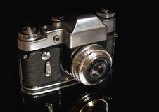 La vecchia macchina da presa su un fondo nero Fotografia Stock