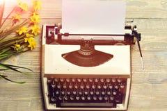 La vecchia macchina da scrivere d'annata con il narciso sbocciante della molla e della carta fiorisce Fotografie Stock Libere da Diritti