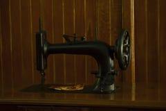 La vecchia macchina per cucire è situata sulla tavola immagine stock