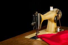 La vecchia macchina per cucire ed il panno rosso Immagini Stock Libere da Diritti