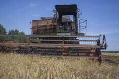 La vecchia mietitrebbiatrice si è accesa sulla raccolta del grano 2 Fotografie Stock Libere da Diritti