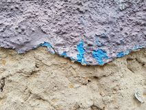 La vecchia parete con il gesso crollato, la cima dei resti del gesso è porpora, il fondo è una superficie di argilla Immagini Stock Libere da Diritti