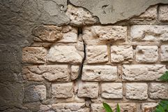 La vecchia parete del mattone bianco con un gesso rotto e incrinato sottragga la priorità bassa fotografia stock libera da diritti