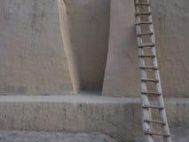 La vecchia parete di pietra è sollievo beige di colore, nella destra alla superficie è una scala di legno alta Fotografia Stock