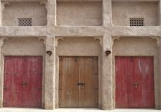 La vecchia parte anteriore della casa con tre ha colorato le porte di legno immagine stock