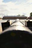 La vecchia pistola antica del cannone tende attraverso il porto sulla casa Immagini Stock