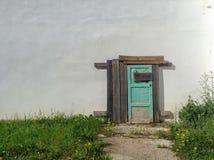La vecchia porta nella parete bianca Fotografia Stock