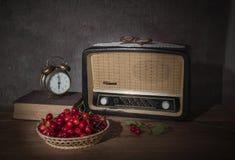 La vecchia radio e le ciliege fresche Fotografie Stock