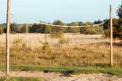 La vecchia rete di pallavolo ha allungato nel campo fotografie stock