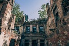 La vecchia rovina rossa abbandonata della casa con mattoni a vista, nociva dal terremoto, guerra o l'altro disastro naturale, ha  Immagini Stock