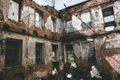 La vecchia rovina rossa abbandonata della casa con mattoni a vista, nociva dal terremoto, guerra o l'altro disastro naturale, ha  Fotografia Stock Libera da Diritti