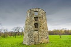 La vecchia rovina rustica del silo del mattone sta alta contro un cielo blu tempestoso Immagini Stock Libere da Diritti