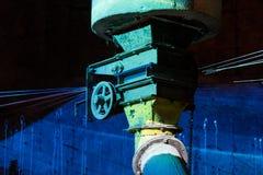 La vecchia ruota del ferro sul tubo industriale colorato allinea Fotografia Stock