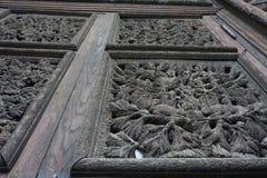 La vecchia scultura di legno dell'inseguimento di anticipa i motivi sulle porte fotografia stock