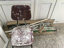 La vecchia sedia con le macchie da pittura e dalla calce è nella stanza Fotografia Stock Libera da Diritti