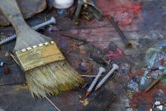 La vecchia spazzola con pittura ha schizzato le viti ed i chiodi Fotografie Stock