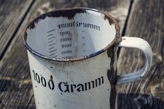 La vecchia tazza metallica d'annata per 1000 grammi sta su fondo di legno Fotografia Stock