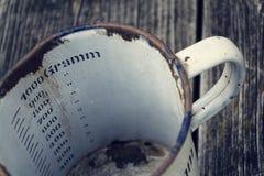 La vecchia tazza metallica d'annata per 1000 grammi sta su fondo di legno Fotografie Stock Libere da Diritti