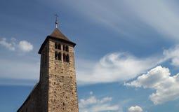 La vecchia torre di chiesa di pietra sul blu drammatico si appanna il fondo immagini stock libere da diritti