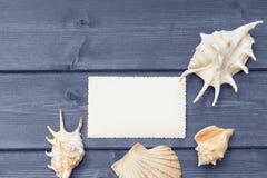 La vecchie foto e conchiglie in bianco che si trovano sullo scrittorio di legno blu Fotografie Stock