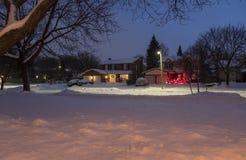 La vecindad suburbana contiene el Lit para arriba con las luces de la Navidad y cubierto con nieve Fotografía de archivo