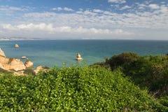 La vegetación verde en paisaje marino con el mar imponente excava los acantilados de la repisa por la playa de Camilo Imagen de archivo