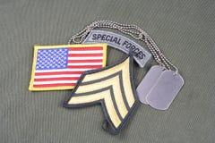 La vegetazione lussureggiante di sergente dell'ESERCITO AMERICANO, forze speciali cataloga, toppa della bandiera e medaglietta pe Immagine Stock
